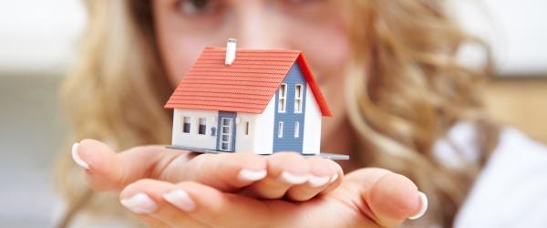 Frau trägt ein kleines Einfamilienhaus auf ihren Händen
